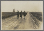 Three soldiers walking up a muddy road. They have ...