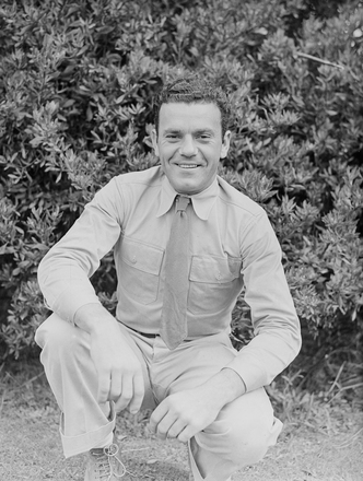[Portrait of a serviceman crouching on grass]