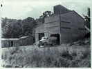 A view of a large shed and two smaller sheds at th...
