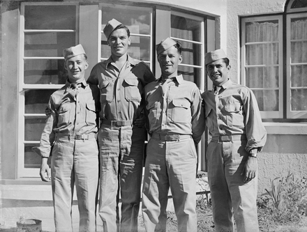 [Group portrait of four servicemen standing in front of the bay window of Tudor…