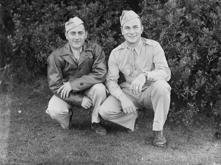 [Portrait of two US soldiers crouching in front of trees]