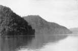 Unidentified lake with forest covered hills.