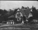 View of lodge with people and a horse-drawn carria...