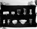 A display of pottery vases and plates on a black v...
