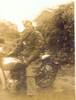 Portrait, Mills, side view, sitting on a motorbike in the garden, in uniform including great coat, cap, gloves, hedge in background - This image may be subject to copyright
