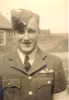 Portrait, head and shoulders: Mills in uniform, cap, wings badge in background stone/brick building - This image may be subject to copyright