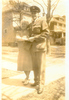 Group, WW2, airman, Mills and his friend Mrs Knoll. Mills has cap, jacket with wings badge, embracing his friend. Standing in front of large houses, trees without leaves, pavement - This image may be subject to copyright