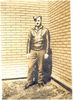 "Portrait, 1942, Mills standing, wearing leather jacket, standing in corner of brick walled area. Mills had written the following on the back of the original photograph ""25-3-42 - Yours Truly. Taken outside the Dormitory at Dunnville on day of the last flight at Dunnville. I was in a hurry to get back into the air. Hence the clothing and worried expression. Note the flying boots."" - This image may be subject to copyright"