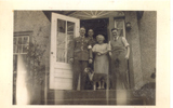 Group, WW2, informal, two airmen in uniform, airman in civilian clothes and woman: From left to right: Lyall King, Jim Shields, Mrs Knoll and Mervyn Jack Mills (NZ414321). Binnie the dog in front, all standing on the steps outside a house. - This image may be subject to copyright